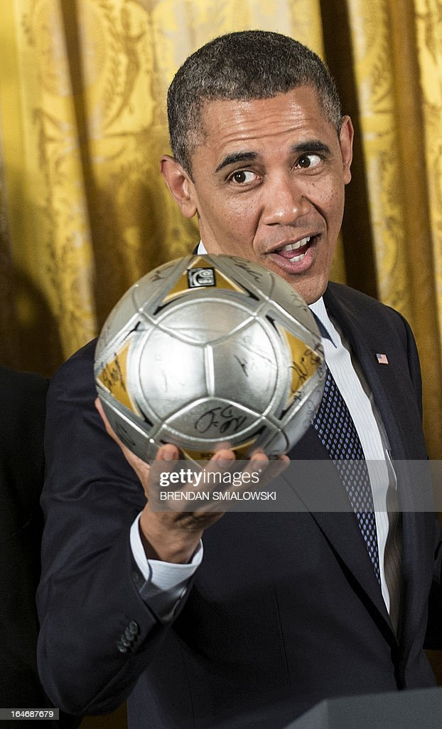 US President Barack Obama holds a soccer ball during an event in the East Room of the White House March 26, 2013 in Washington, DC. Obama hosted the event to honor the 2012 MLS Cup Champions, the Los Angeles Galaxy and the 2012 Stanley Cup Champions Los Angeles Kings. AFP PHOTO/Brendan SMIALOWSKI