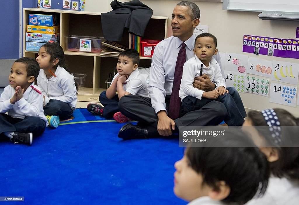 US President Barack Obama holds Marcus Wesby on his lap as he sits with children during a tour of a Pre-K classroom at Powell Elementary School prior to speaking on the Fiscal Year 2015 budget in Washington, DC, March 4, 2014. AFP PHOTO / Saul LOEB