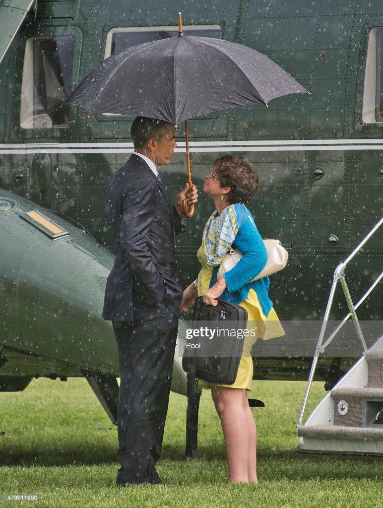 S President Barack Obama holds the umbrella during a rain shower for Valerie Jarrett Senior Advisor to the President and Assistant to the President...