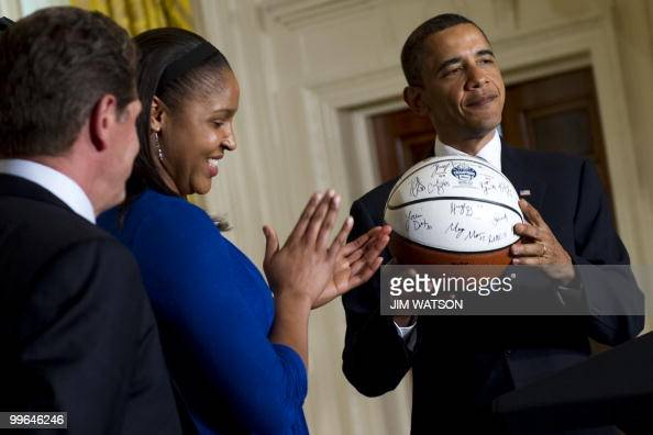 US President Barack Obama holds up a basketball given to him by the NCAA champion University of Connecticut women's basketball team as Forward Maya...