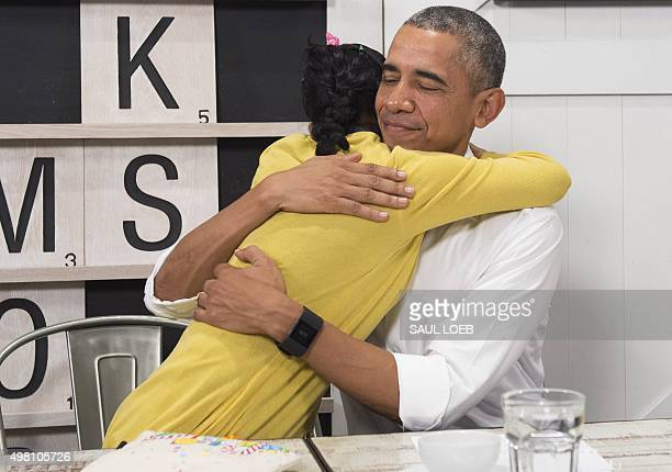 US President Barack Obama hugs a 16yearold refugee girl from Myanmar that was subjected to human trafficking and will now be moving to the United...
