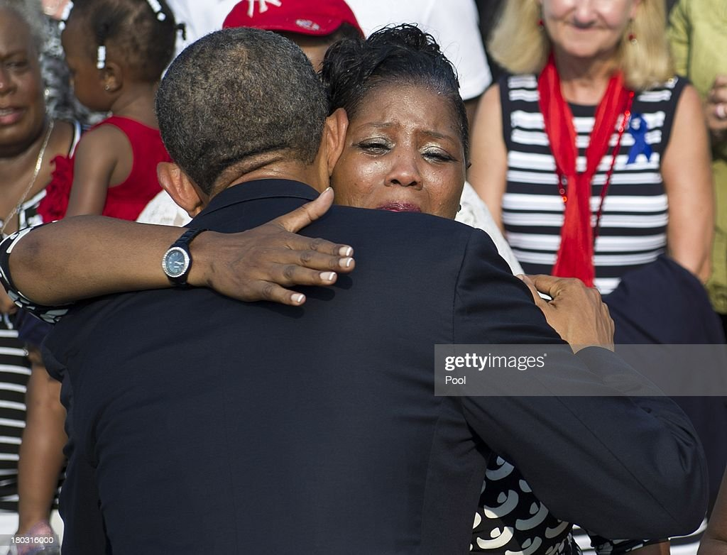 S. President <a gi-track='captionPersonalityLinkClicked' href=/galleries/search?phrase=Barack+Obama&family=editorial&specificpeople=203260 ng-click='$event.stopPropagation()'>Barack Obama</a> hugs a audience member during a ceremony in observance of the terrorist attacks of 9/11 as Defense Secretary Chuck Hagel (L) and Chairman of the Joint Chiefs of Staff Gen. Martin Dempsey listen at the Pentagon September 11, 2013 in Arlington, Virginia. Family members of the Pentagon attack victims and survivors of the attack gathered to hear from Obama and other leaders at the National 9/11 Pentagon Memorial near the place where terrorists drove a jetliner into the Department of Defense headquarters in 2001.