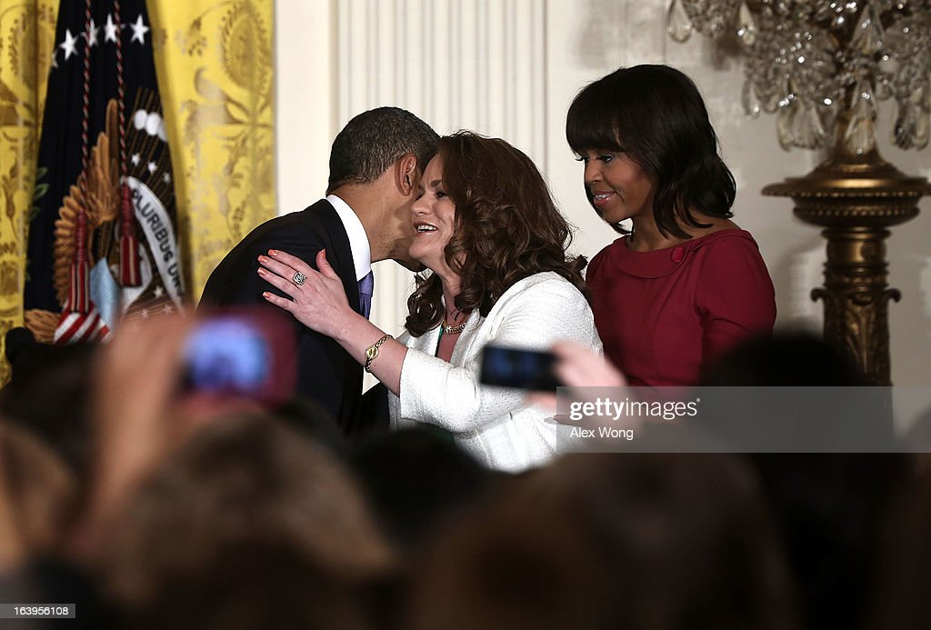 U.S. President <a gi-track='captionPersonalityLinkClicked' href=/galleries/search?phrase=Barack+Obama&family=editorial&specificpeople=203260 ng-click='$event.stopPropagation()'>Barack Obama</a> (L) hugs Amanda McMillan (2nd L) of Mississippi as first lady <a gi-track='captionPersonalityLinkClicked' href=/galleries/search?phrase=Michelle+Obama&family=editorial&specificpeople=2528864 ng-click='$event.stopPropagation()'>Michelle Obama</a> (R) looks on during a Women's History Month Reception in the East Room of the White House March 18, 2013 in Washington, DC. President Obama was accompanied by first lady <a gi-track='captionPersonalityLinkClicked' href=/galleries/search?phrase=Michelle+Obama&family=editorial&specificpeople=2528864 ng-click='$event.stopPropagation()'>Michelle Obama</a> to participate in the event.