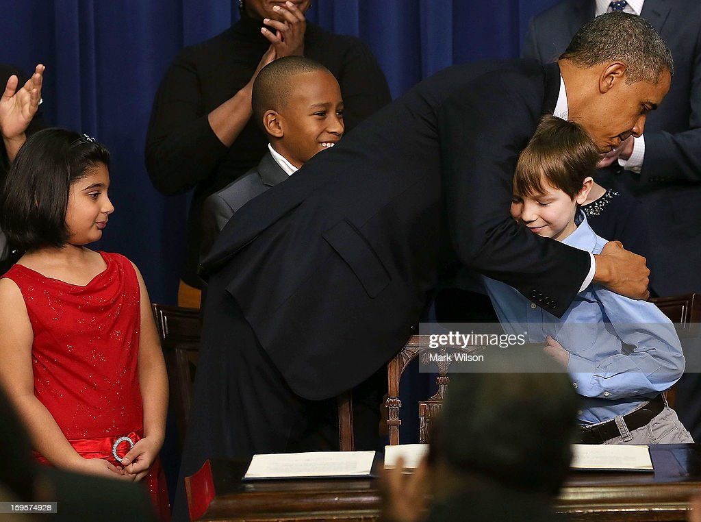 U.S. President Barack Obama hugs children who wrote letters to the White House about gun violence, (L-R) Hinna Zeejah, Taejah Goode, and Grant Fritz, after announcing the administration's new gun law proposals in the Eisenhower Executive Office building, on January 16, 2012 in Washington, DC. One month after a massacre that left 20 school children and 6 adults dead in Newtown, Connecticut, the president unveiled a package of gun control proposals that include universal background checks and bans on assult weapons and high-capacity magazines.