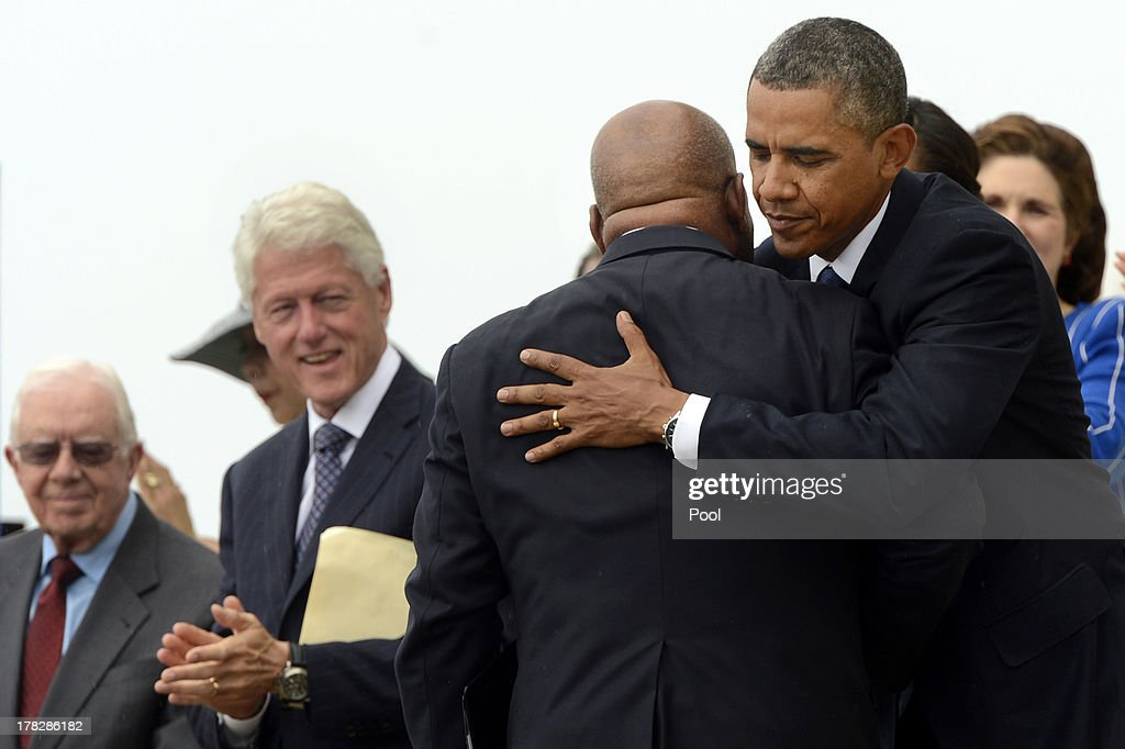 US President Barack Obama (R) hugs civil rights leader and Rep. John Lewis (D-GA) (2nd-R) after Lewis delivered remarks, as former US President Jimmy Carter (L) and former US President Bill Clinton look on, during the 'Let Freedom Ring' commemoration event August 28, 2013 in Washington, DC. The event was to commemorate the 50th anniversary of Dr. Martin Luther King Jr.'s 'I Have a Dream' speech and the March on Washington for Jobs and Freedom.