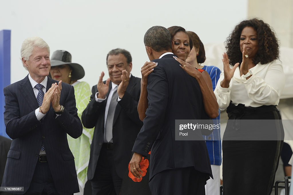 US President Barack Obama (C) hugs First Lady Michelle Obama (2-R) as former US President Bill Clinton (L) and Oprah Winfrey (R) look on, during the 'Let Freedom Ring' commemoration event, at the Lincoln Memorial August 28, 2013 in Washington, DC. The event was to commemorate the 50th anniversary of Dr. Martin Luther King Jr.'s 'I Have a Dream' speech and the March on Washington for Jobs and Freedom.