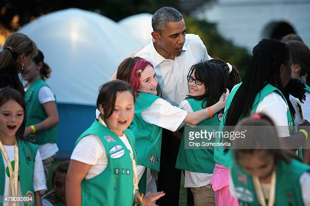 US President Barack Obama hugs Girl Scouts who traveled from across the country for a campout on the South Lawn of the White House June 30 2015 in...