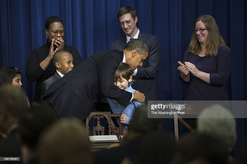 JANUARY 16 -- President Barack Obama hugs Grant Fritz, 8, as his mom, Elisabeth Carlin, right, looks on during an event to unveil a package of proposals to unveil a package of proposals to reduce gun violence during an event at the Eisenhower Executive Office Building in Washington, D.C., on Wednesday, January 16, 2013. Also pictured from left are Hinna Zeejah, 8, Taejah Goode, 10, with his mom, Kimberly Graves; and Dr. Theophil Stokes. The children who wrote letters to the President were invited to the event with their parents.