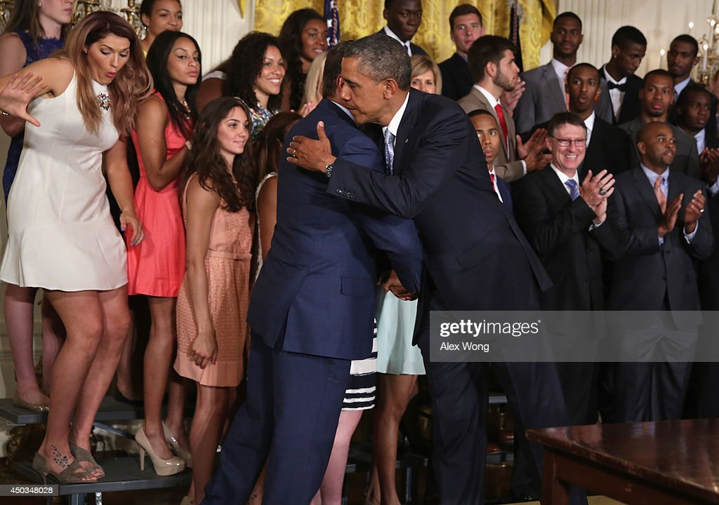 U.S. President <a gi-track='captionPersonalityLinkClicked' href=/galleries/search?phrase=Barack+Obama&family=editorial&specificpeople=203260 ng-click='$event.stopPropagation()'>Barack Obama</a> (R) hugs head coach <a gi-track='captionPersonalityLinkClicked' href=/galleries/search?phrase=Geno+Auriemma&family=editorial&specificpeople=704607 ng-click='$event.stopPropagation()'>Geno Auriemma</a> as center <a gi-track='captionPersonalityLinkClicked' href=/galleries/search?phrase=Stefanie+Dolson&family=editorial&specificpeople=7369130 ng-click='$event.stopPropagation()'>Stefanie Dolson</a> (L) of the University of Connecticut women's basketball team slips off the riser during an East Room event at the White House June 9, 2014 in Washington, DC. President Obama hosted the NCAA Champion UConn Huskies Men's and Women's Basketball teams to honor the teams and their 2014 NCAA Championships.