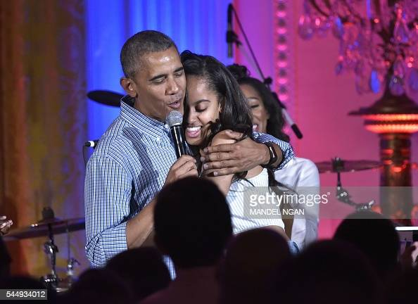 President Barack Obama hugs his daughter Malia on her birthday during an Independence Day Celebration for military members and administration staff...