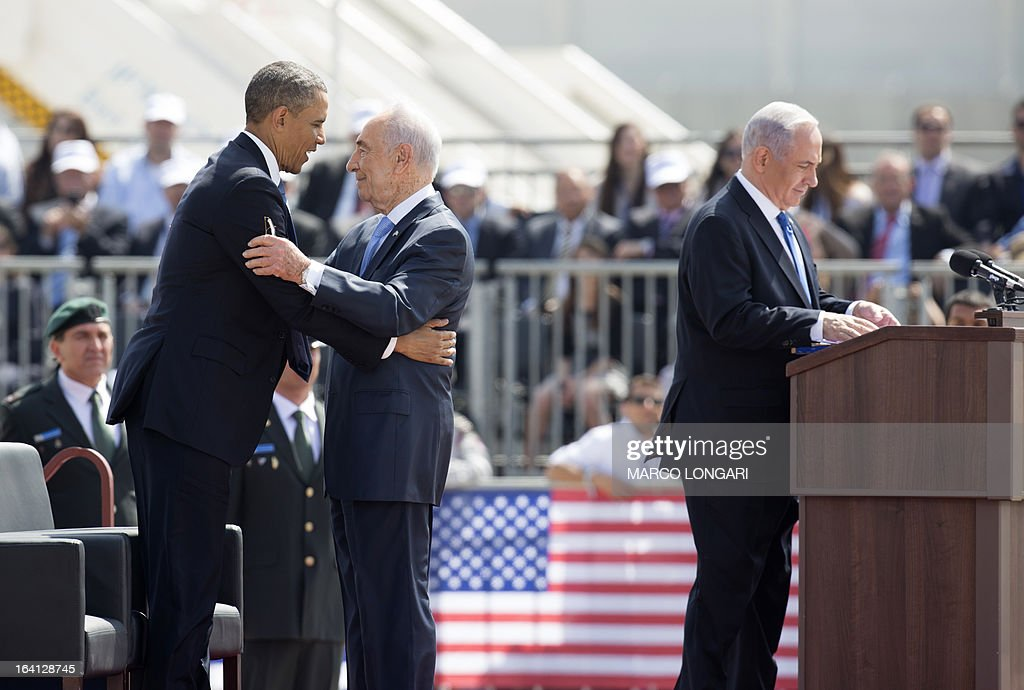 US President Barack Obama (L) hugs Israeli President Shimon Peres (C) as Prime Minister Benjamin Netanyahu (R) finishes his speech during a welcome ceremony at Ben Gurion International Airport on March 20, 2013 near Tel Aviv. Obama landed in Israel for the first time as US president, on a mission to ease past tensions with his hosts and hoping to paper over differences on handling Iran's nuclear threat.