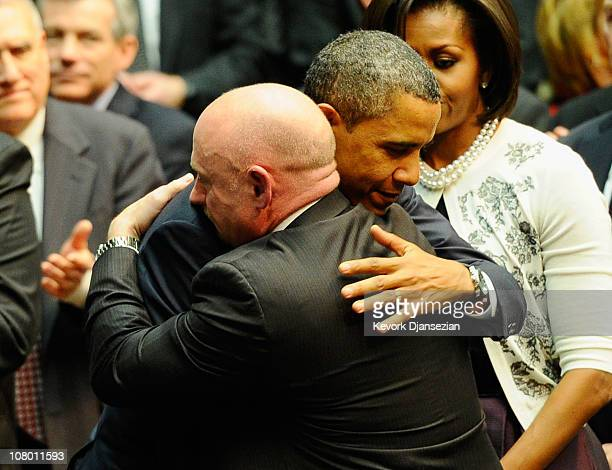 President Barack Obama hugs NASA astronaut Mark Kelly husband of US Rep Gabrielle Giffords as he arrives to attend the event 'Together We Thrive...