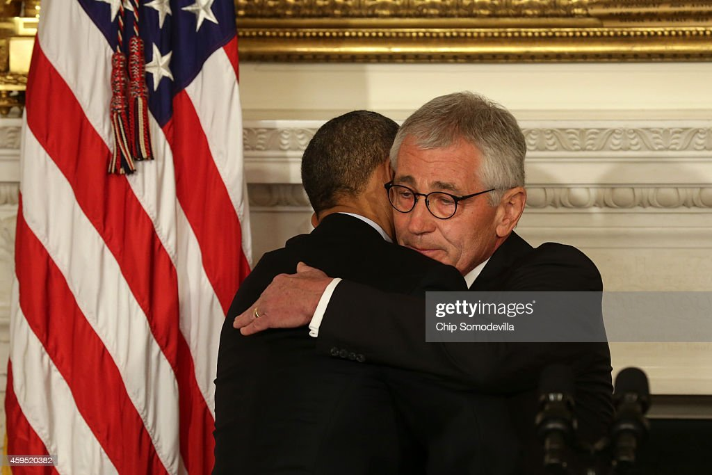 U.S. President Barack Obama (L) hugs Secretary of Defense Chuck Hagel during a press conference announcing Hagel's resignation in the State Dining Room of the White House November 24, 2014 in Washington, DC. Sources say Hagel plans to remain in office until his successor is confirmed by the Senate.