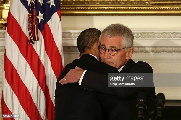 S President Barack Obama hugs Secretary of Defense Chuck Hagel during a press conference announcing Hagel's resignation in the State Dining Room of...