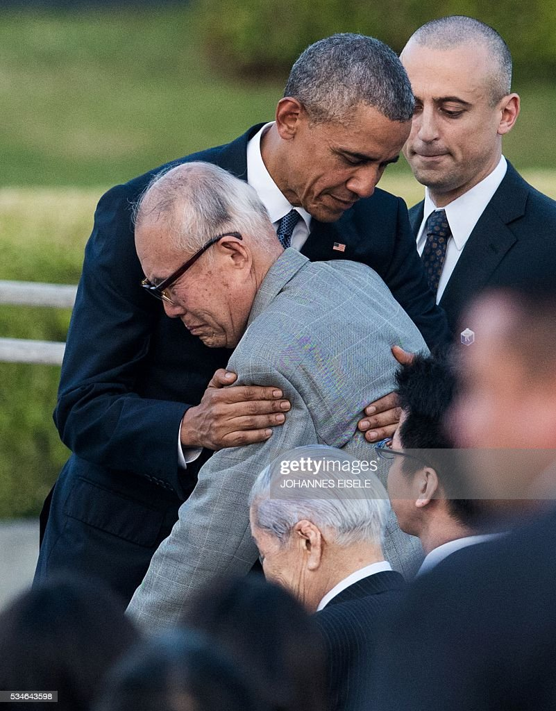 US President Barack Obama (L) hugs Shigeaki Mori (C), a survivor of the 1945 atomic bombing of Hiroshima, during a visit to the Hiroshima Peace Memorial Park in Hiroshima on May 27, 2016. Obama paid moving tribute on May 27 to victims of the world's first nuclear attack, during a historic visit to Hiroshima. / AFP / JOHANNES