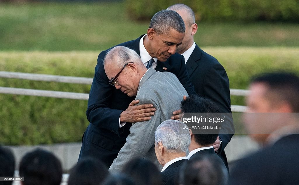 US President Barack Obama hugs a survivor of the atomic bombing of Hiroshima at the Hiroshima Peace Memorial park cenotaph in Hiroshima on May 27, 2016. Obama became the first sitting US leader to visit the site that ushered in the age of nuclear conflict. / AFP / JOHANNES