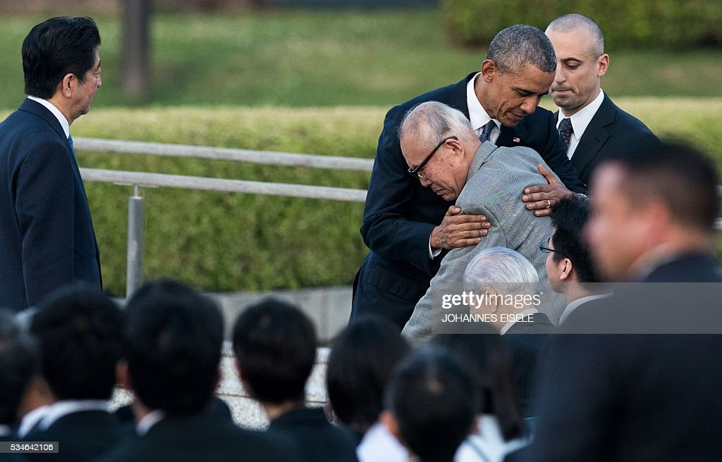 US President Barack Obama hugs Mori Shigeaki, a survivor of the atomic bombing of Hiroshima, as Japanese Prime Minister Shinzo Abe (L) looks on at the Hiroshima Peace Memorial park cenotaph in Hiroshima on May 27, 2016. Obama became the first sitting US leader to visit the site that ushered in the age of nuclear conflict. / AFP / JOHANNES