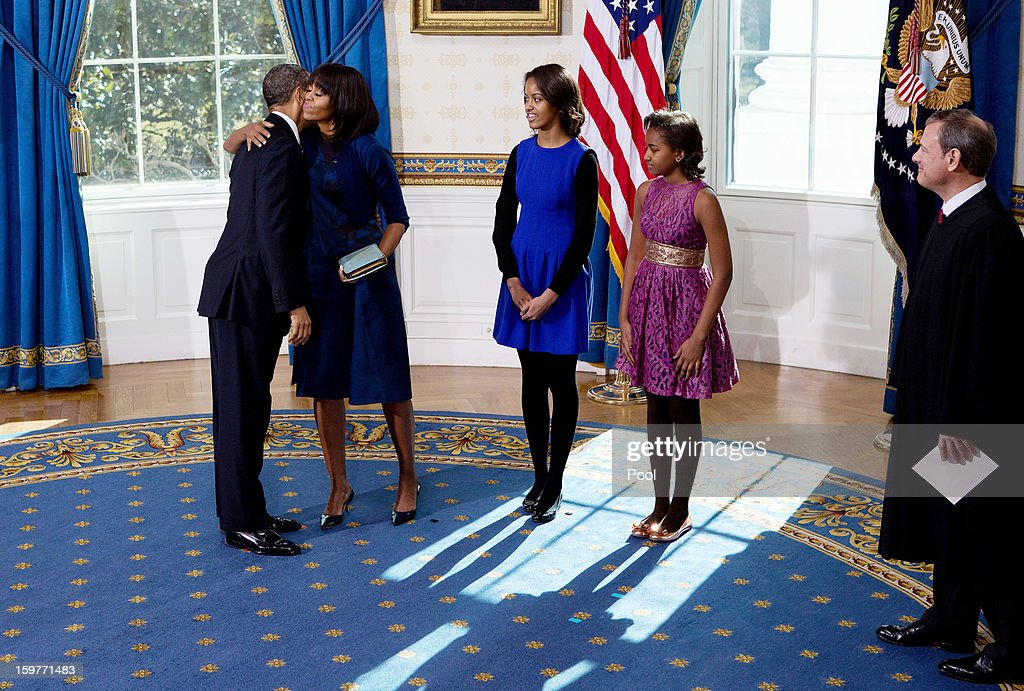 President <a gi-track='captionPersonalityLinkClicked' href=/galleries/search?phrase=Barack+Obama&family=editorial&specificpeople=203260 ng-click='$event.stopPropagation()'>Barack Obama</a> (L) hugs the first lady <a gi-track='captionPersonalityLinkClicked' href=/galleries/search?phrase=Michelle+Obama&family=editorial&specificpeople=2528864 ng-click='$event.stopPropagation()'>Michelle Obama</a> (2nd L) as daughters Malia (3rd L) and Sasha(2nd R) and U.S. Supreme Court Chief Justice John Roberts look on after taking the oath of office in the Blue Room of the White House January 20, 2013 in Washington, DC. Obama and U.S. Vice President Joe Biden were officially sworn in a day before the ceremonial inaugural swearing-in.