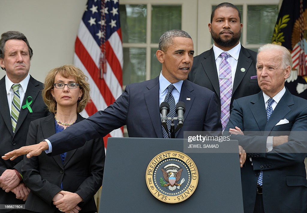 US President Barack Obama is accompanied by former lawmaker Gabrielle Giffords (L), vice president Joe Biden (R) and family members of Newtown school shooting victims as he speaks on gun control at the Rose Garden of the White House in Washington, DC, on April 17, 2013. Obama on Wednesday slammed what he called a 'minority' in the US Senate for blocking legislation that would have expanded background checks on those seeking to buy guns. AFP PHOTO/Jewel Samad