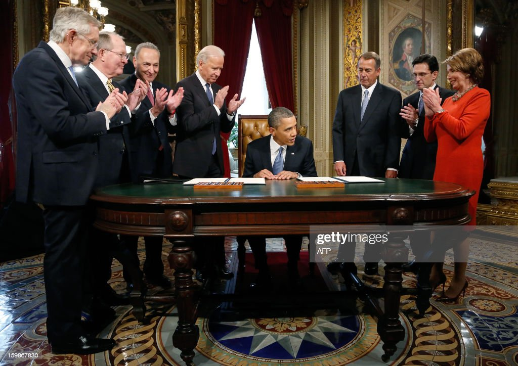US President Barack Obama (C) is applauded by Senate Majority Leader Harry Reid ,D-NV, L-R: Senator Lamar Alexander ,R-TN, Senator Chuck Schumer ,D-NY, Vice President Joe Biden, House Speaker John Boehner ,R-OH, House Majority Leader Eric Cantor ,R-VA, and House Minority Leader Nancy Pelosi ,D-CA,after signing a proclamation to commeorate the inauguration, entitled a National Day of Hope and Resolve, directly after swearing-in ceremonies in the US Capitol in Washington, January 21, 2013. AFP PHOTO / Jonathan Ernst / POOL