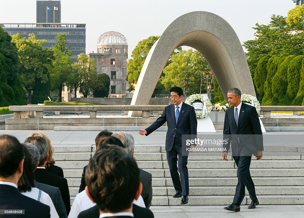 US Presdent Barack Obama (R) is escorted by Japanese Prime Minister Shinzo Abe after laying wreaths in front of a cenotaph to offer a prayer for victims of the atomic bombing in 1945, at the Hiroshima Peace Memorial Park on May 27, 2016. Obama on May 27 paid moving tribute to victims of the world's first nuclear attack. / AFP / POOL / KIMIMASA