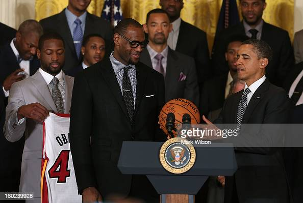 S President Barack Obama is given a ball from LeBron James during an event to honor the NBA champion Miami Heat in the East Room at the White House...