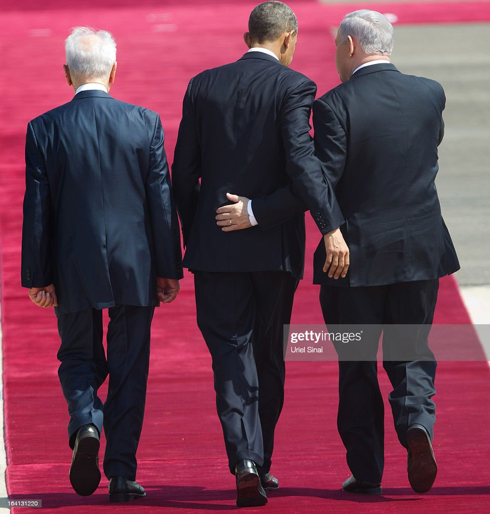US President Barack Obama (C) is greeted by Israeli President Shimon Peres (L) and Israeli Prime Minister Benjamin Netanyahu (R) during an official welcoming ceremony on his arrival at Ben Gurion International Airport on March 20, 2013 near Tel Aviv, Israel. This will be Obama's first visit as President to the region, and his itinerary will include meetings with the Palestinian and Israeli leaders as well as a visit to the Church of the Nativity in Bethlehem.
