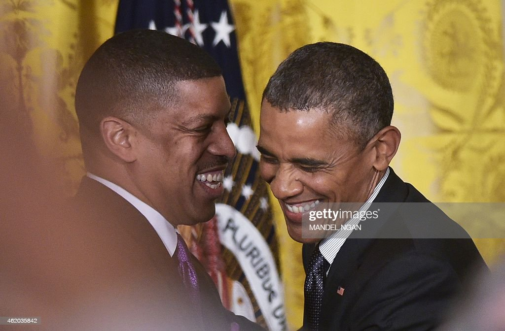 US President Barack Obama is greeted by US Conference of Mayors President, Sacremento Mayor Kevin Johnson (L), after introducing him to the US Conference of Mayors on January 23, 2015 in the East Room of the White House in Washington, DC.
