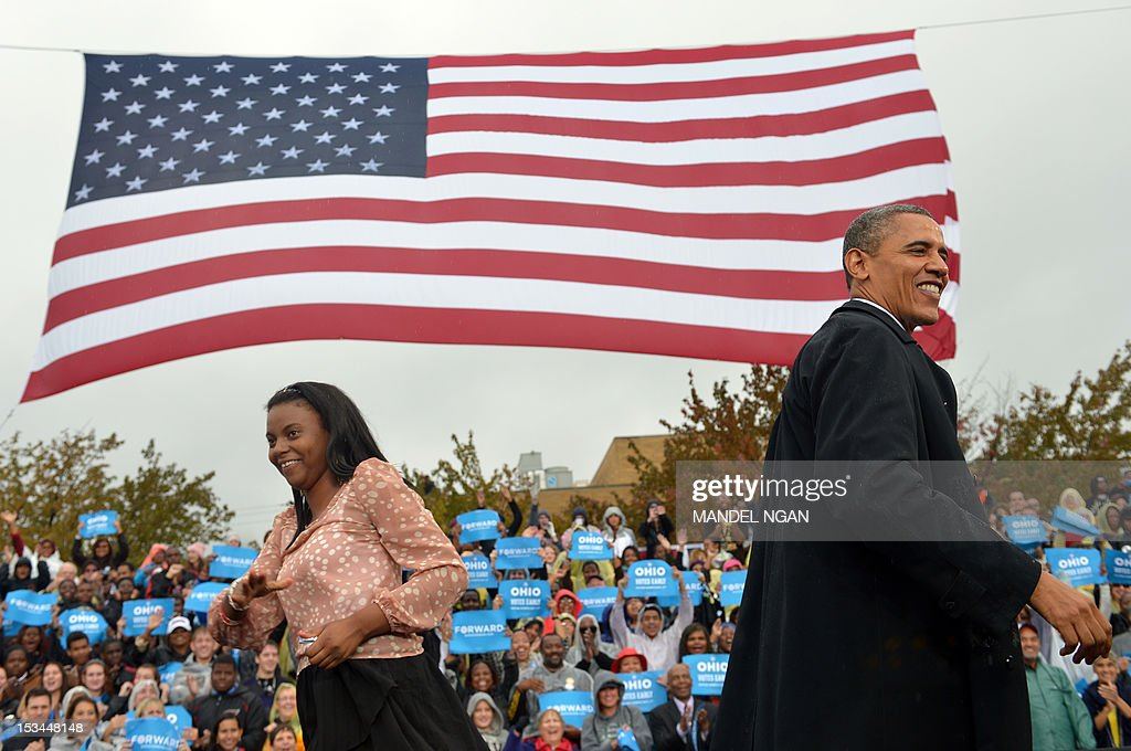 US President Barack Obama is helped with his coat by Tatiana Brown as he arrives on stage during a campaign rally October 5, 2012 at Cleveland State University in Cleveland, Ohio. AFPHOTO/Mandel NGAN