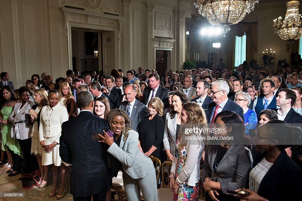 US President Barack Obama is hugged as he greets audience members after an event to celebrate the 2015 WNBA Champions, Minnesota Lynx, in the East Room of the White House June 27, 2016 in Washington, DC. / AFP / Brendan Smialowski