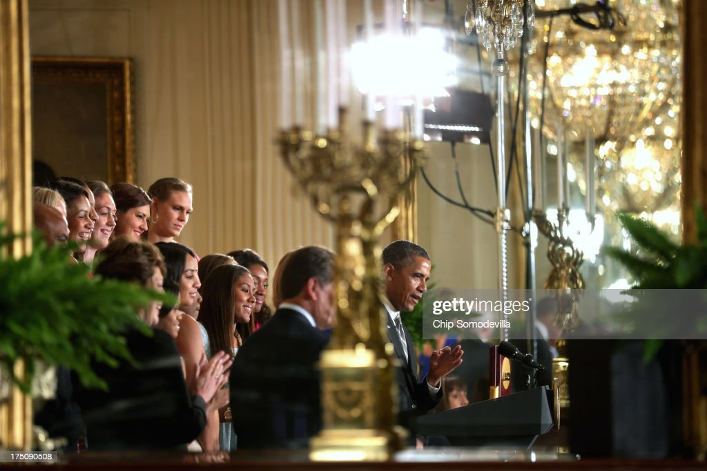 President Barack Obama (R) is reflected in a mirror in the East Room as he hosts the 2013 NCAA champion University of Connecticut Huskies Women's basketball players at the White House July 31, 2013 in Washington, DC. Obama hosted the team after they defeated the University of Louisville on April 9 to win their eighth national championship.
