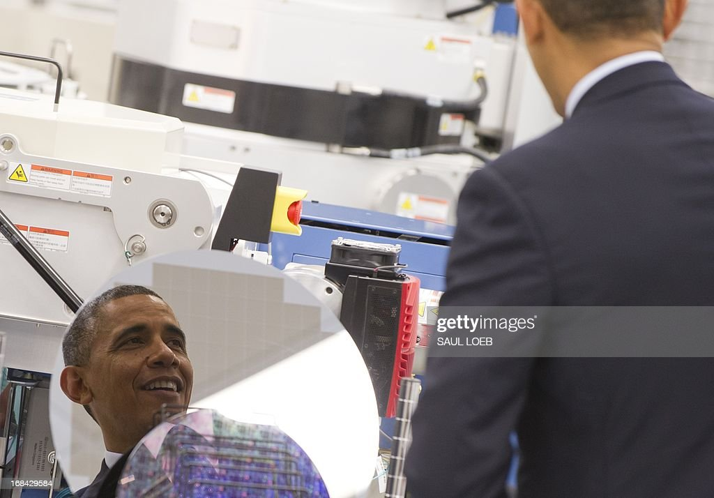 US President Barack Obama is reflected in a silicon wafer as he tours Applied Materials, a manufacturer of systems for polishing the surface of unfinished semiconductor chips, prior to speaking on the economy and job creation in Austin, Texas, on May 9, 2013. AFP PHOTO / Saul LOEB