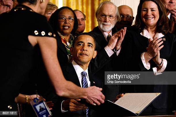 S President Barack Obama is surrounded by stemcell research supporters members of Congress and members of his cabinet while signing an Executive...