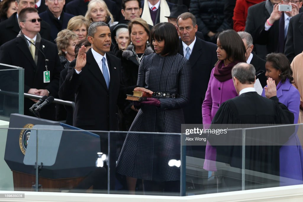 U.S. President Barack Obama is sworn in by Supreme Court Chief Justice John Roberts as first lady Michelle Obama and daughters, Sasha Obama and Malia Obama look on during the public ceremonial inauguration on the West Front of the U.S. Capitol January 21, 2013 in Washington, DC. Barack Obama was re-elected for a second term as President of the United States.