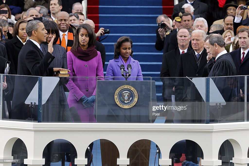 S President Barack Obama is sworn in by Supreme Court Chief Justice John Roberts as first lady Michelle Obama daughters Malia Obama and Sasha Obama...