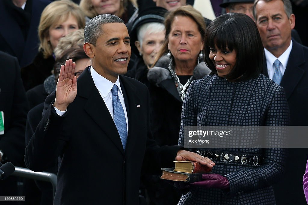 U.S. President Barack Obama is sworn in during the public ceremony as First lady Michelle Obama looks on during the presidential inauguration on the West Front of the U.S. Capitol January 21, 2013 in Washington, DC. Barack Obama was re-elected for a second term as President of the United States.
