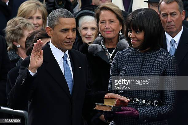 S President Barack Obama is sworn in during the public ceremony as First lady Michelle Obama looks on during the presidential inauguration on the...