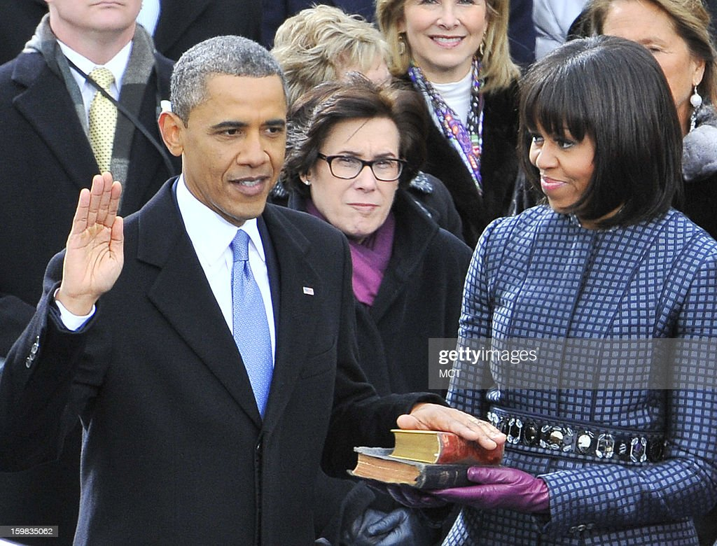 President Barack Obama is sworn-in for a second term as the President of the United States by Supreme Court Chief Justice John Roberts during his public inauguration ceremony at the U.S. Capitol in Washington, D.C. on January 21, 2013. Michelle Obama holds the bible.