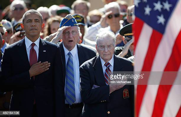 S President Barack Obama joins WWII Veterans during the playing of the national anthem at a ceremony at the Normandy American Cemetery on the 70th...