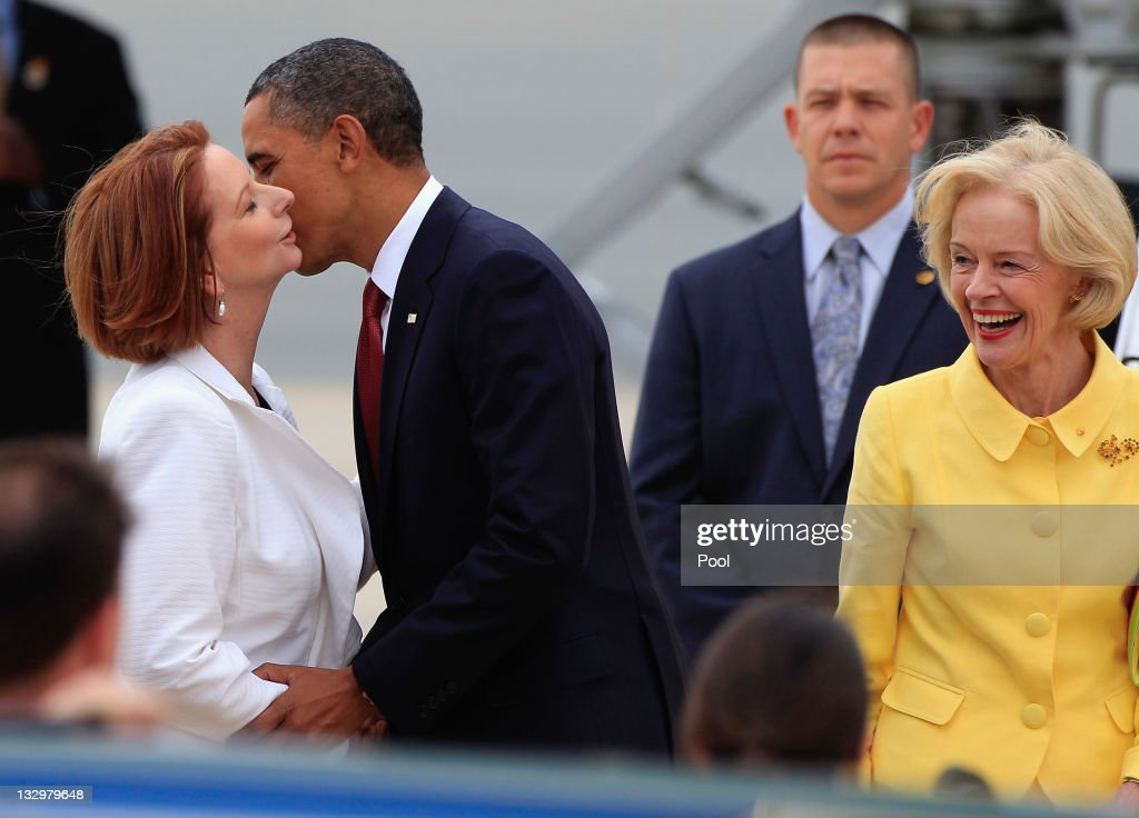 U.S. President <a gi-track='captionPersonalityLinkClicked' href=/galleries/search?phrase=Barack+Obama&family=editorial&specificpeople=203260 ng-click='$event.stopPropagation()'>Barack Obama</a> kisses Australian Prime Minister <a gi-track='captionPersonalityLinkClicked' href=/galleries/search?phrase=Julia+Gillard&family=editorial&specificpeople=787281 ng-click='$event.stopPropagation()'>Julia Gillard</a> as the Governor General <a gi-track='captionPersonalityLinkClicked' href=/galleries/search?phrase=Quentin+Bryce&family=editorial&specificpeople=2602196 ng-click='$event.stopPropagation()'>Quentin Bryce</a> (R) smiles, after arriving at Fairbairn Defence Establishment on the first day of his 2-day visit to Australia, on November 16, 2011 in Canberra, Australia. The President will today receive a Cermeonial Welcome, attend a bi-lateral meeting and hold a joint media conference with <a gi-track='captionPersonalityLinkClicked' href=/galleries/search?phrase=Julia+Gillard&family=editorial&specificpeople=787281 ng-click='$event.stopPropagation()'>Julia Gillard</a>, and attend a Parliamentary Dinner this evening, before addressing Parliament and heading to Darwin tomorrow.