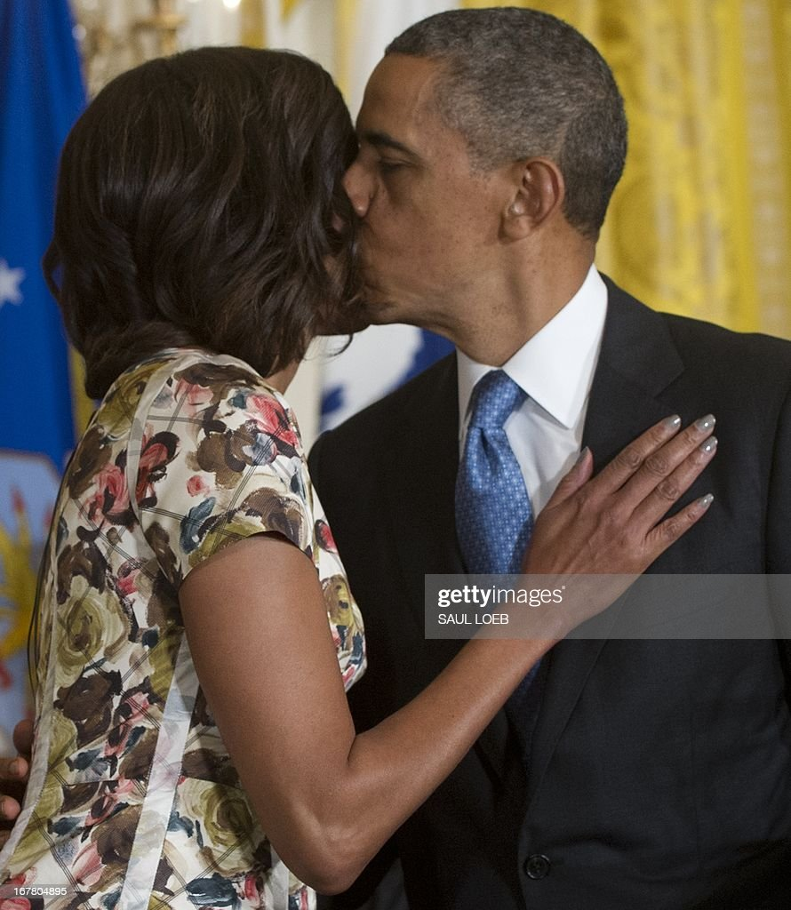 US President Barack Obama kisses First Lady Michelle Obama after speaking about the Joining Forces hiring initiative for military veterans and spouses in civilian jobs during an event in the East Room of the White House in Washington on April 30, 2013. Since President Obama challenged American businesses to hire US military veterans and spouses in August 2011, they have hired or trained 290,000 military veterans and spouses and now pledge to hire or train an additional 435,000 veterans and military spouses by 2018. AFP PHOTO / Saul LOEB