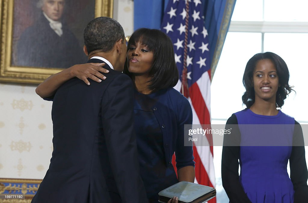 U.S. President Barack Obama (L) kisses first lady Michelle Obama (C) as daughter Malia looks on in the Blue Room of the White House January 20, 2013 in Washington, DC. Obama and U.S. Vice President Joe Biden were officially sworn in a day before the ceremonial inaugural swearing-in.