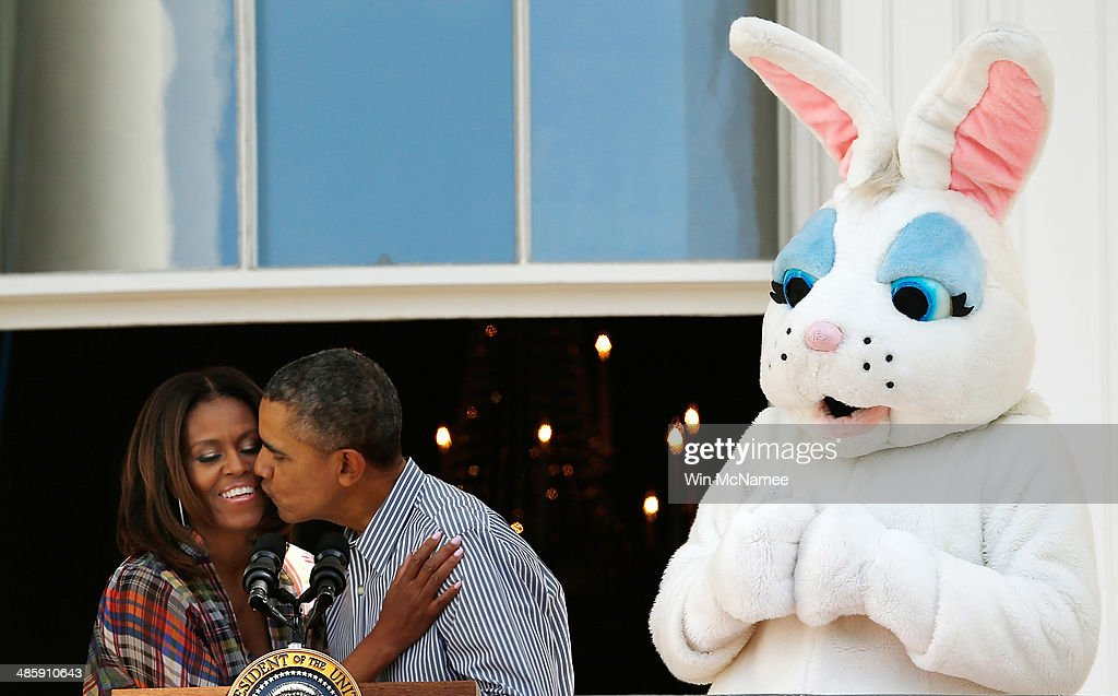 S President Barack Obama kisses first lady Michelle Obama at the annual White House Easter Egg Roll on the South Lawn April 21 2014 in Washington DC...