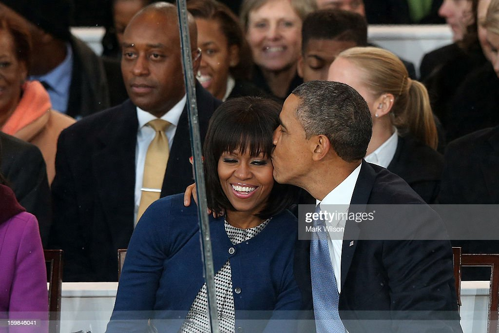 U.S. President Barack Obama (R) kisses first lady Michelle Obama on the reviewing stand as the presidential inaugural parade winds through the nation's capital January 21, 2013 in Washington, DC. Barack Obama was ceremonially sworn in for a second term as President of the United States.