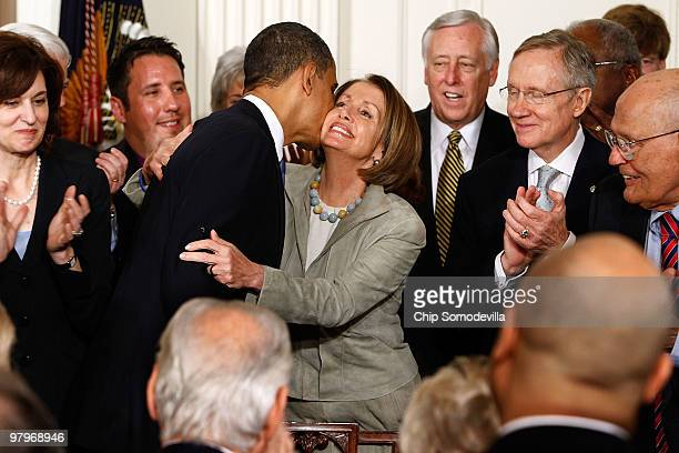 S President Barack Obama kisses Speaker of the House Nancy Pelosi after signing the Affordable Health Care for America Act during a ceremony with...