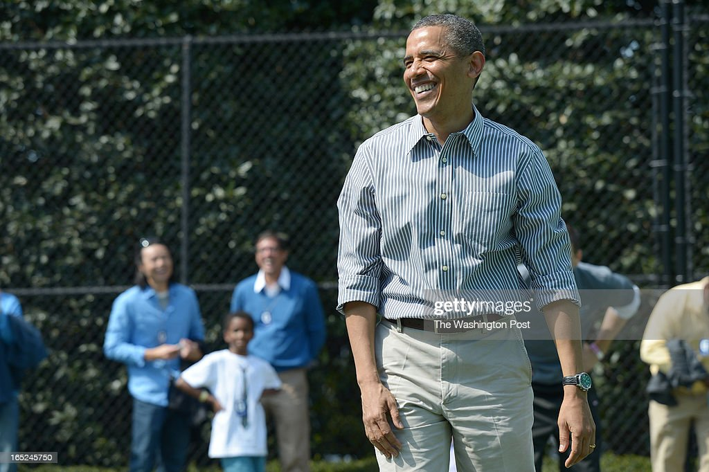 President Barack Obama laughs with others during a basketball station during the annual White House Easter Egg Roll on Monday April 01, 2013 in Washington, DC. Kid President, Robbie Novak was in attendance as well as Washington Wizards players and others.
