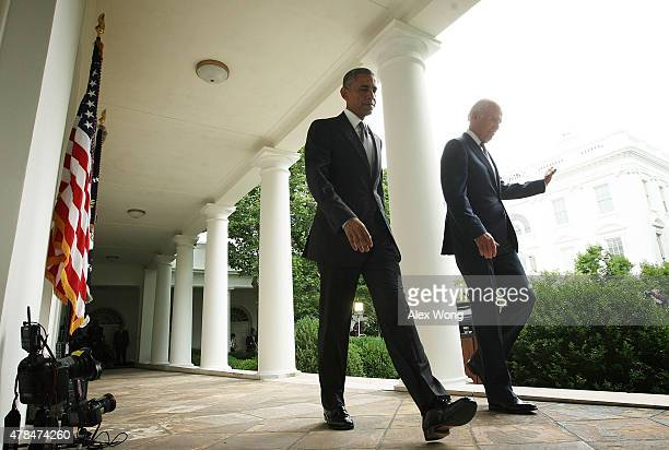 S President Barack Obama leaves with Vice President Joe Biden after he gave a statement on the Supreme Court health care decision in the Rose Garden...