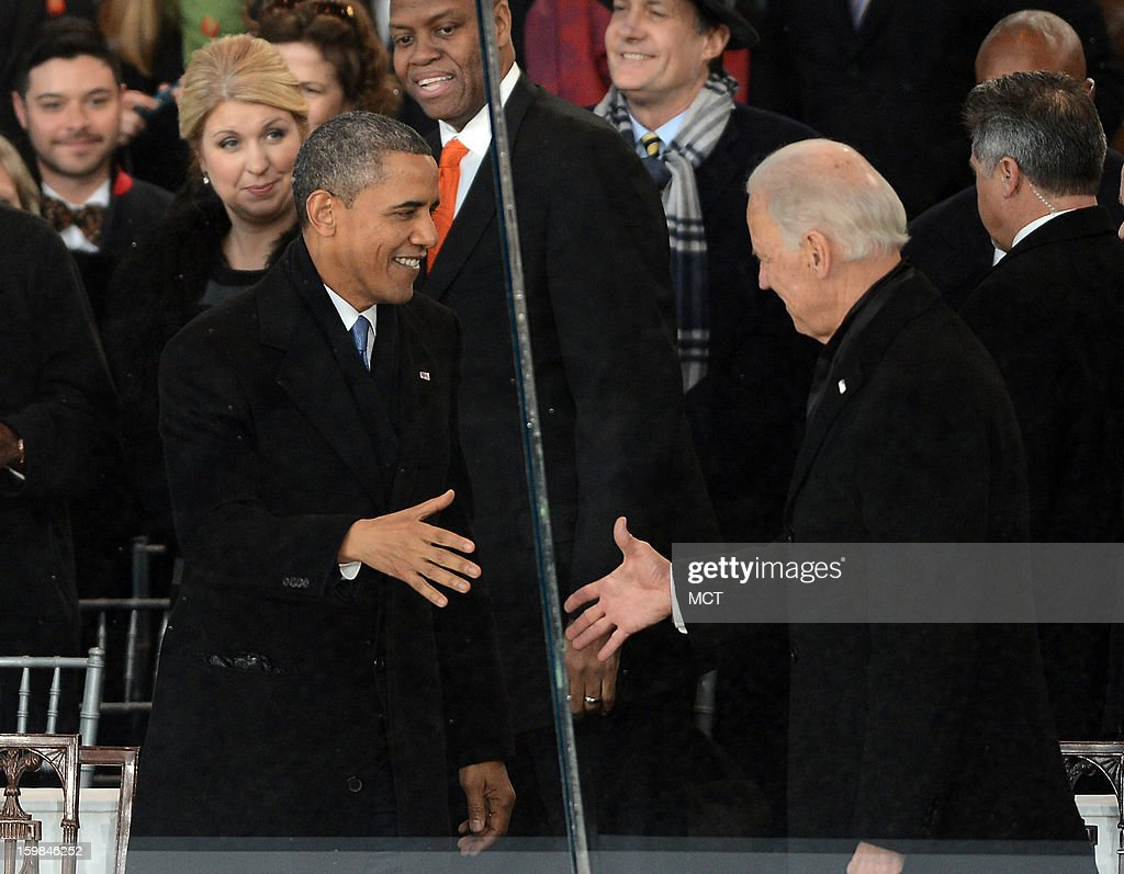 U.S. President Barack Obama, left, and U.S. Vice President Joe Biden shake hands ask they take their place in the review stand for the Inauguration Parade for the second term of President Obama in Washington, D.C., Monday, January 21, 2013.