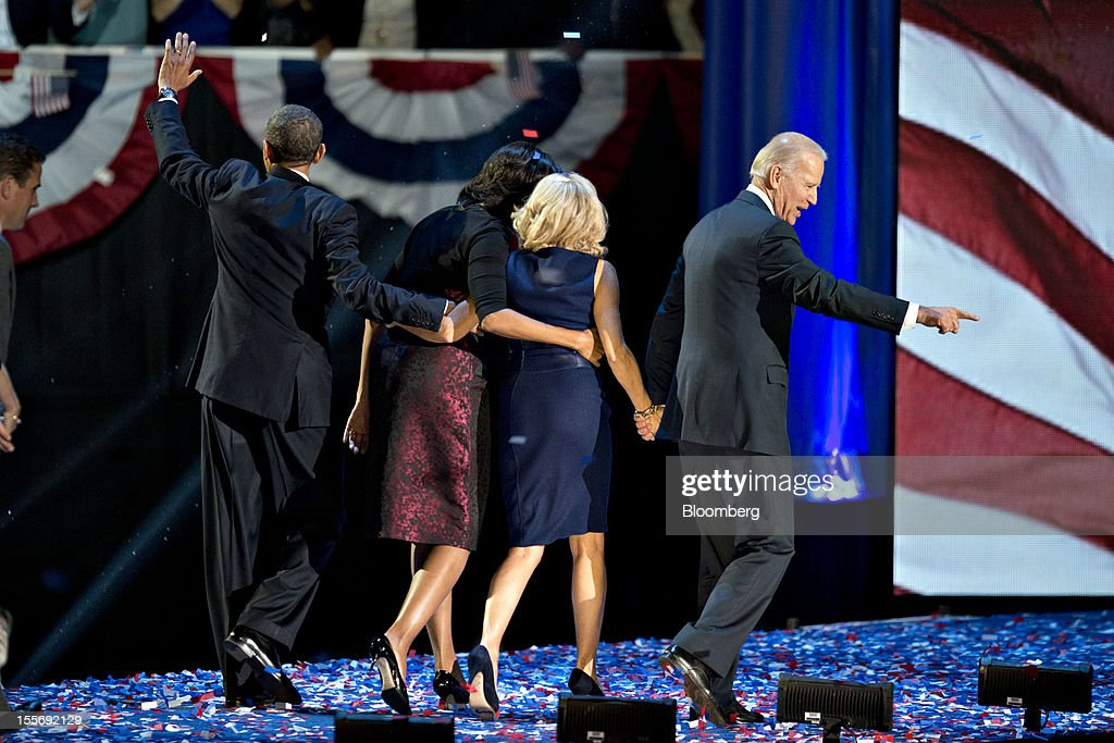 U.S. President Barack Obama, left, and U.S. Vice President Joseph 'Joe' Biden, right, gesture to the crowd as they walk off the stage with First Lady Michelle Obama, second left, and Jill Biden, wife of Joe Biden, during an election night rally in Chicago, Illinois, U.S., in the early morning on Wednesday, Nov. 7, 2012. Obama, the post-partisan candidate of hope who became the first black U.S. president, won re-election today by overcoming four years of economic discontent with a mix of political populism and electoral math. Photographer: Daniel Acker/Bloomberg via Getty Images