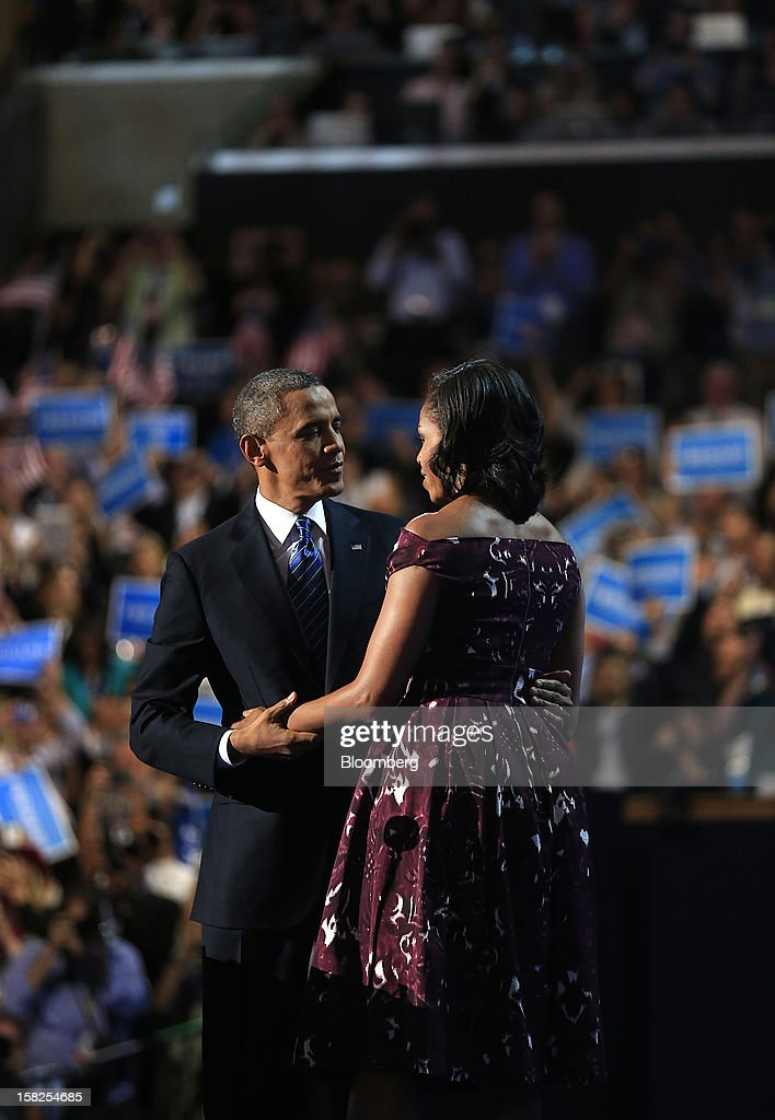 U.S. President Barack Obama, left, embraces First Lady Michelle Obama while arriving at the podium to speak during day three of the Democratic National Convention (DNC) in Charlotte, North Carolina, U.S., on Thursday, Sept. 6, 2012. President Barack Obama's prime-time nomination acceptance speech tonight at the DNC is aimed at convincing voters that a slow economic recovery will accelerate if they give him a second term. Photographer: Andrew Harrer/Bloomberg via Getty Images